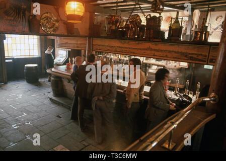 Old traditional pub interior with men drinking at the bar - Stock Image