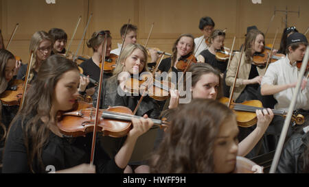 Selective focus view of student musicians playing instruments in orchestra recital - Stock Image