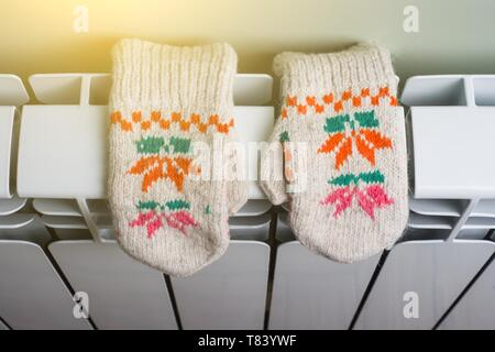 Radiator heating panel with knitted baby mittens - Stock Image