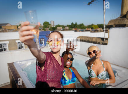 Portrait confident, carefree young women friends drinking champagne in sunny rooftop hot tub - Stock Image