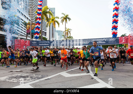 Runners sprint away from the starting line of the 2014 Mercedes-Benz Corporate Run in Miami, Florida, USA. - Stock Image