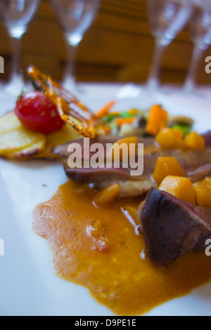 Goose breast with peaches served with a medley of winter vegetables and Anna potatoes - Stock Image