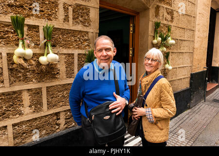 Spain, Cadiz, Calle Sopranis, happy tourists outside vegetable shop with onions outside - Stock Image