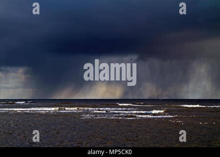 Heavy rain showers moving down the North Yorkshire coast at Scarborough. - Stock Image
