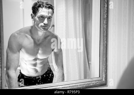 Attractive shirtless man with muscular body and sixpack abs looking at his reflection in bathroom mirror - Stock Image
