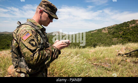 U.S. Army Staff Sgt. Jonathan Houston, a competitor in the Drill Sergeant Of The Year Competition, uses his compass during land navigation course on Fort Sill, OK., Aug. 28, 2018. The Drill Sergeant Of The Year Competition is one of the most physically demanding and mentally tough challenges any Soldier can face in a U.S. Army competition. (U.S. Army photo by Pfc. Joshua Hugley) - Stock Image
