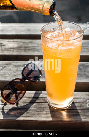 Refreshing amber cold drink being poured into a glass over ice - Stock Image