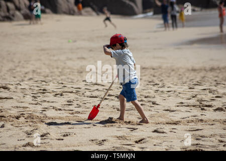 small boy walking on beech with his spade - Stock Image