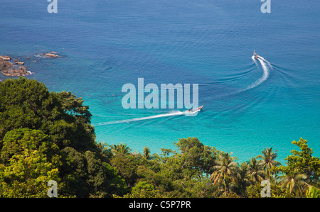 Longtail boats in clear blue water of the andaman Sea Phuket Thailand - Stock Image