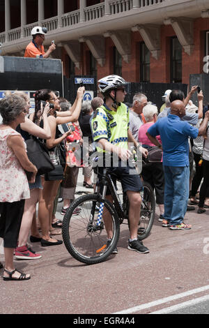 Male Western Australian police bicycle officer keeping an eye on proceedings at a public event. - Stock Image