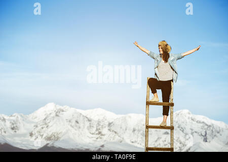 Happy girl stands on wooden staircase with raised arms against snowy mountains - Stock Image
