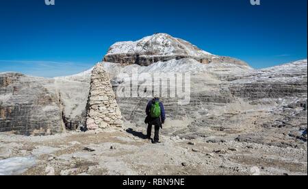 Tourist on the rock of the Sass Pordoi. View towards Piz Boe Mountain, Sella Group, Dolomites, Trentino province, Italy. - Stock Image