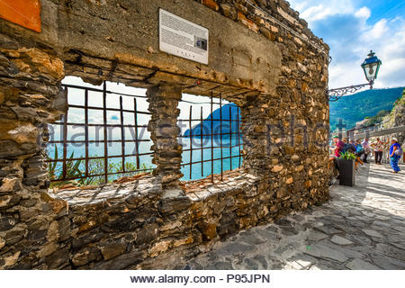 Tourists stop to enjoy the view of the Ligurian Sea on the walking path between the old and new sections of Monterosso Al Mare, Cinque Terre, Italy - Stock Image