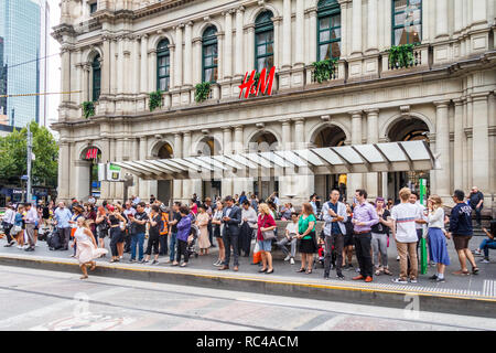 Melbourne, Australia - 21st February 2018: People waiting for the tram on Bourke Street outside the Old Post Office. The street is in the heart of the - Stock Image