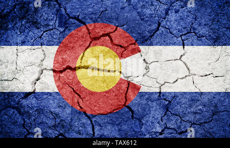 State of Colorado flag, state of the Western United States, on dry earth ground texture background - Stock Image