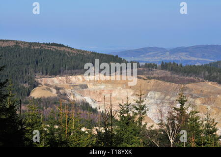 Quarry seen from a distance in Rudawy Janowickie or Landeshut Ridge  mountains. - Stock Image