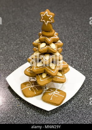 Homemade Gingerbread Christmas Tree: Decorated gingerbread cookies stacked to resemble a christmas tree with presents beneath. - Stock Image