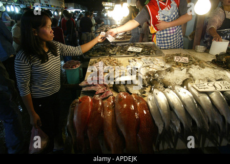 A woman purchases fish from a vendor at the City Market in Baguio City. - Stock Image