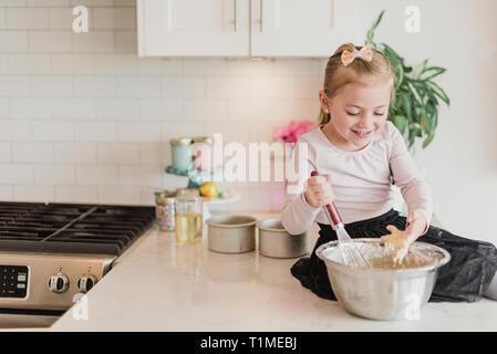 Smiling girl baking on kitchen counter - Stock Image