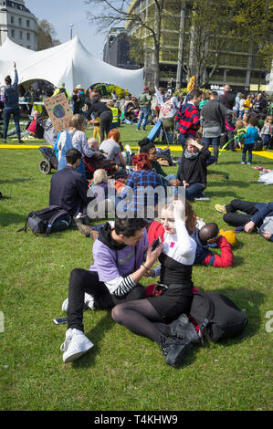 Demonstratos sit on the grass at the Extinction Rebellion demonstration in Marble Arch - Stock Image