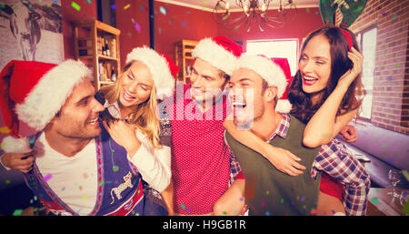 Composite image of men wearing christmas wearing giving women piggyback rides - Stock Image