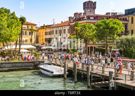 SIRMIONE, LAKE GARDA, ITALY - SEPTEMBER 2018: People on the harbourside in Sirmione on Lake Garda - Stock Image