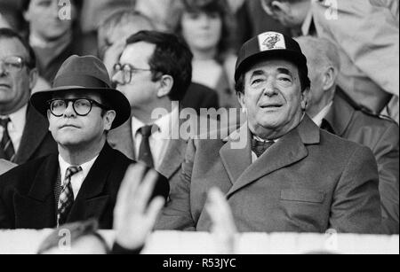 Elton John and Robert Maxwell watching the Oxford United v Watford football match. Final score 1-1. League Division One. Elton John had announced days before that he was selling his 90 per cent holding in Watford FC. 21st November 1987. - Stock Image