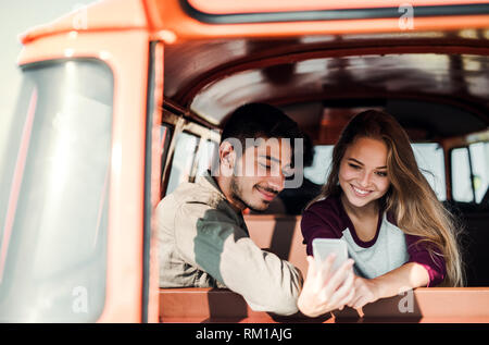A group of young friends on a roadtrip through countryside, taking selfie. - Stock Image