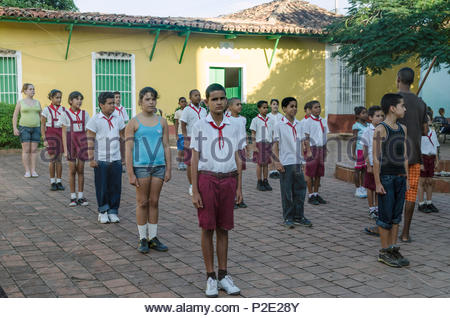 Cuban school children lined up in square being addressed by a teacher. Trinidad, Cuba. - Stock Image