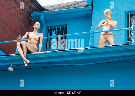 Two gold mannequins sit atop a store roof in Kensington Market in downtown Toronto, Ontario, Canada - Stock Image