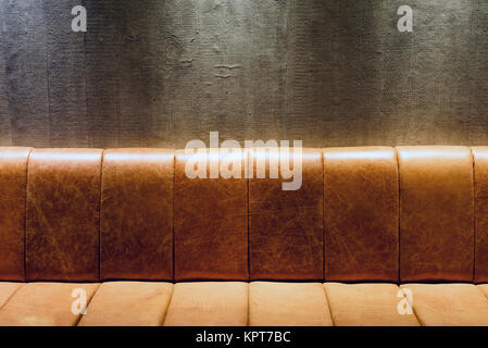 Aged vintage retro themed brown leather couch at night inside with nobody and copy space area for interior design - Stock Image