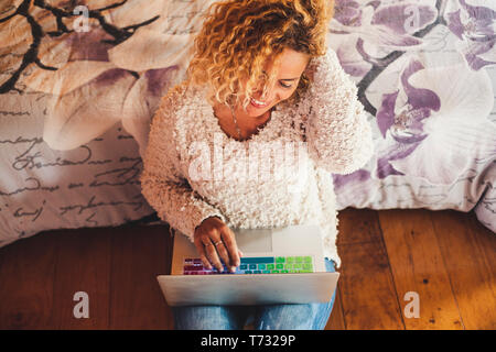 Above view cheerful beautiful caucasian curly woman working with laptop computer writing on the keyboard and smiling to the screen sitting on the wood - Stock Image