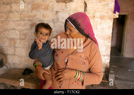 A Bishnoi girl smiles and waves while being held by her mother. - Stock Image