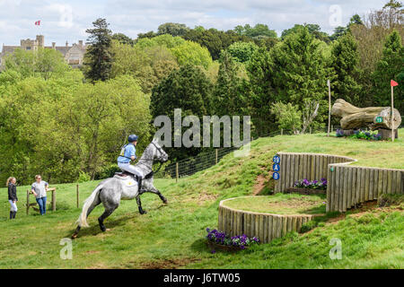 Rockingham Castle, Corby, UK. 21st May, 2017. James Rushbrooke and his horse Rowland run uphill towards a log obstacle - Stock Image