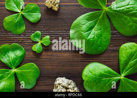 Shamrocks and Pyrite on Dark Wood Table with Space for Copy - Stock Image