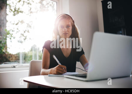 Portrait of young woman sitting in kitchen with headphones writing note. Female studying at home with laptop. - Stock Image