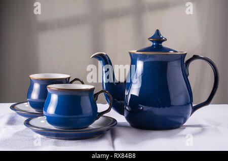 Old-fashioned teapot and matching cups and saucers - Stock Image