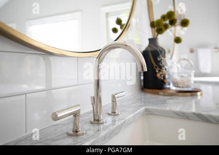 Bathroom sink in a white marble vanity with white tiles and mirror - Stock Image