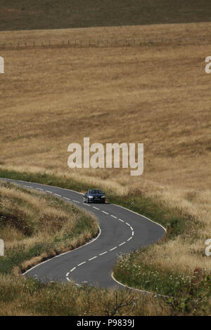 Beachy Head, UK - July 14 2018:  A road cuts through the country grasslands of the Eastbourne Downland Estate by Beachy Head on a hot summers day on 14 July 2018. Temperatures raised to 27 degrees and is expected to stay high for another month. The cliff, the highest chalk sea cliff in Britain rises to 162 metres above sea level and unfortunately one of the most notorious suicide spots in the world. Credit: David Mbiyu - Stock Image