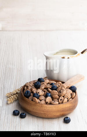 Chocolate  chip cookie cereal with blueberry and milk on white wooden table - Stock Image