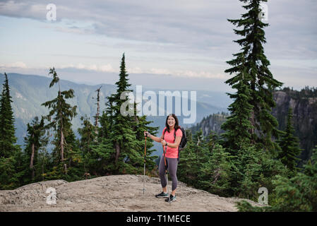 Portrait happy young woman hiking at mountaintop, Dog Mountain, BC, Canada - Stock Image