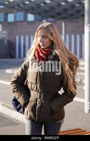 candid street style image of young woman waiting at bus station on a sunny day in winter - Stock Image