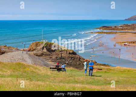 6 July 2018: Bude, Cornwall, UK - Tourists on Compass Hill looking down over busy Summerleaze Beach during the summer heatwave, as people cool off in  - Stock Image