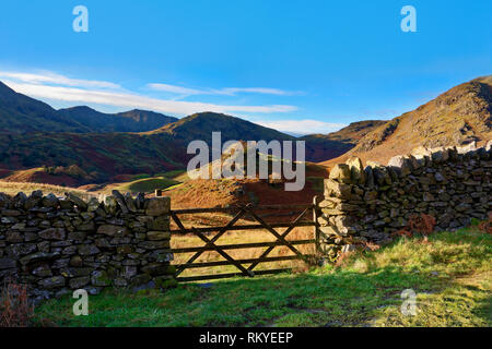 A view of a traditional dry stone wall and wooden gate in the hilly landscape of the English Lake District. - Stock Image