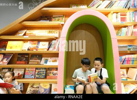 (190218) -- BEIJING, Feb. 18, 2019 (Xinhua) -- Du Zihao (1st R), a volunteer librarian, introduces a book to a little boy at Jimo Bookstore in Qingdao City, east China's Shandong Province, July 19, 2018. Chinese readers, many of whom had switched to e-reading devices and online bookstores, are now flocking back to traditional stores as they are offering a wider range of new products.    The Bookdao New Publishing Institute, a consultancy to the country's publishing and book selling industry, surveyed 62 chains and found that some 65 percent plan to open more than five new stores this year, and - Stock Image