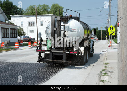 Tar or asphalt spreader truck parked in construction zone. - Stock Image