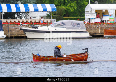 A steward wearing a raincoat and yellow sou'wester hat sits in a wooden rowing boat moored in the River Thames on a wet day at Henley Royal Regatta - Stock Image