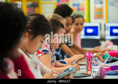Junior high school girl students studying at desk in classroom - Stock Image