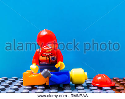 Poznan, Poland - February 12, 2019: Lego female rescue doctor performing first aid on a construction worker laying on the ground. - Stock Image