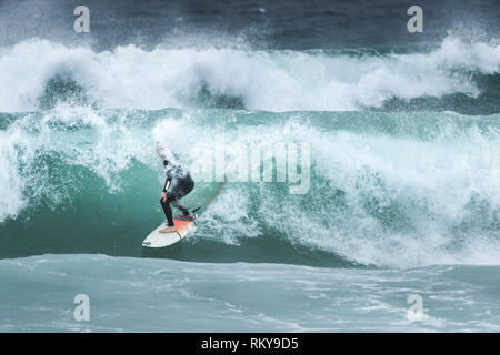A surfer riding a wave at Fistral Beach in Newquay in Cornwall. - Stock Image